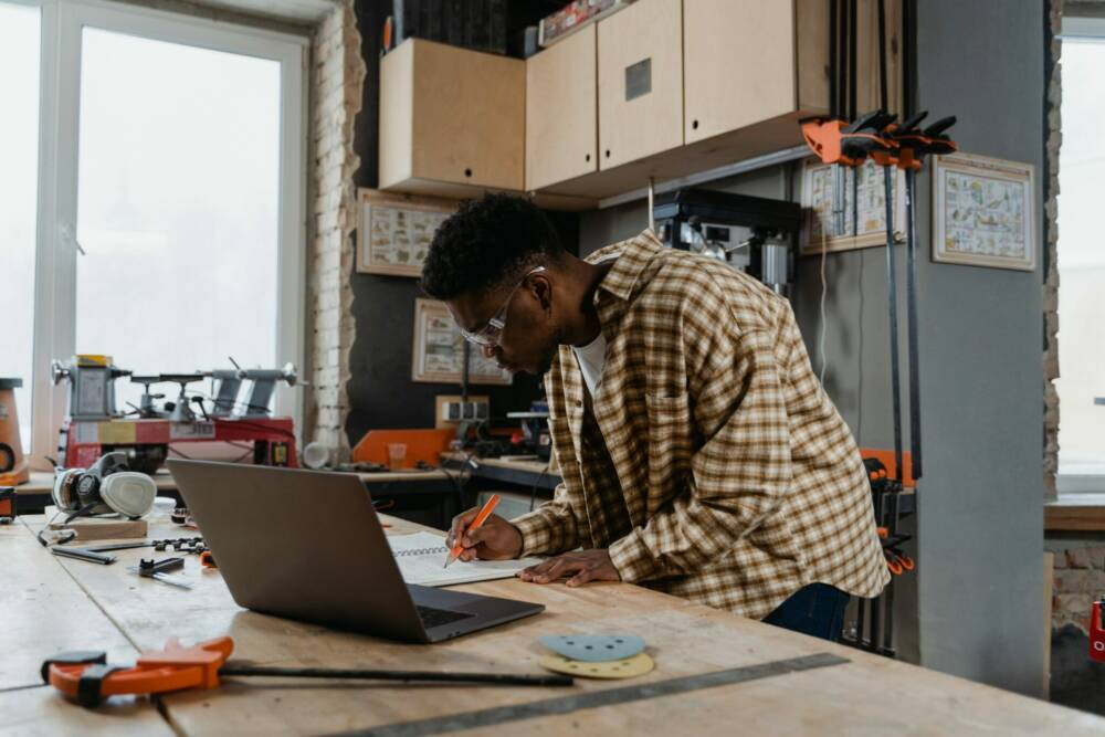 A guy in his workshop with a laptop